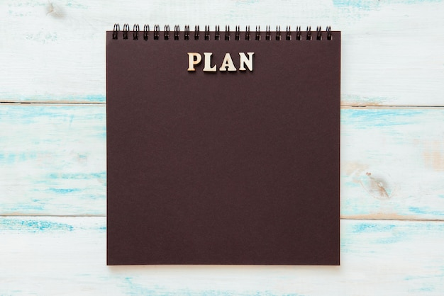 Black notepad with the word plan