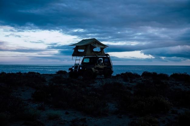 黒いオフロードの美しい冒険家の車、ルーフテント付きの小さな家、旅行や世界中の素晴らしい旅に最適