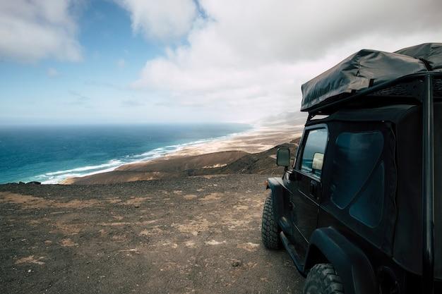 誰もいない野生のビーチの素晴らしい景色を望む谷の頂上に駐車した黒いオフロード車