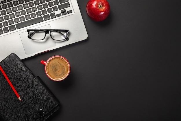 Стол черный офисный стол с пустой экран портативный компьютер, ноутбук, чашка кофе, красное яблоко и другой офис. вид сверху с копией пространства.