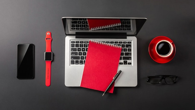 Black office desk table with blank screen laptop computer, notebook, watch, mobile phone and red cup of coffee. top view.