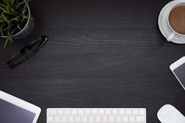 コンピュータノートブックとコーヒーカップを備えた黒のオフィスデスクテーブル