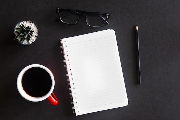 커피 컵, 선인장, 안경, 연필 및 노트북이있는 검은 색 사무실 책상