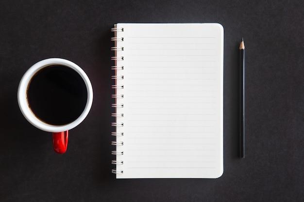 커피 컵, 연필 및 노트북 검은 사무실 책상