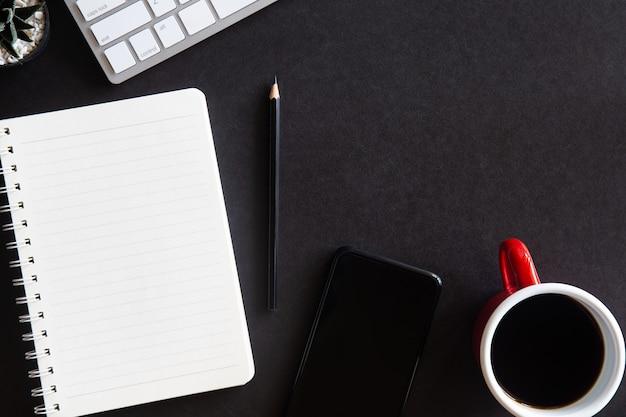커피 컵, 스마트 폰, 키보드, 연필 및 노트북이있는 검은 색 사무실 책상