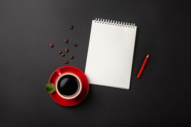 Black office desktop with red cup, beans of coffee and notebook. top view with copy space