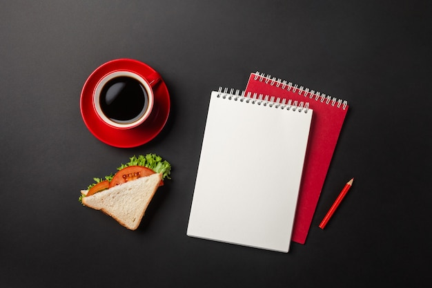 Black office desktop with red cup of coffee, notebook and sandwich for lunch. top view with copy space