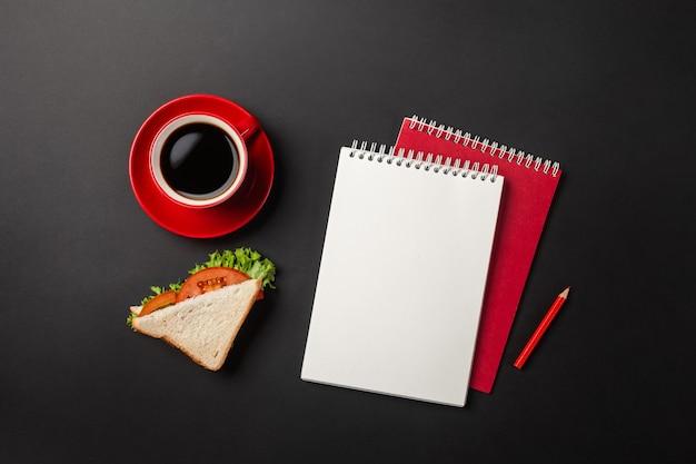Черный рабочий стол офиса с красной чашкой кофе, блокнотом и бутербродом на обед. вид сверху с копией пространства