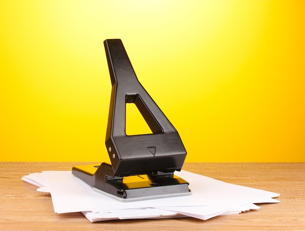Black office hole punch with paper on yellow background