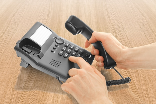 Black office telephone with hand dialing