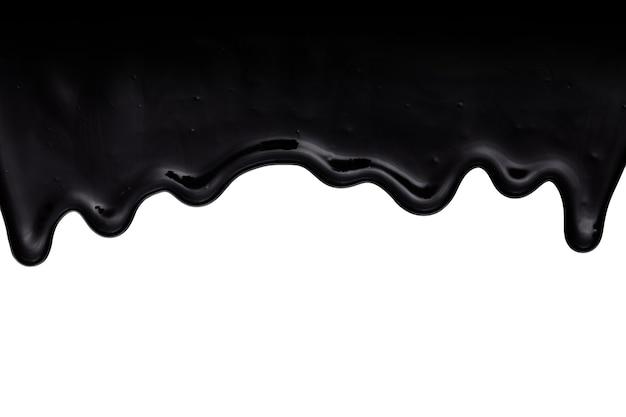 白い背景に分離された黒い油のようなタール状または樹脂状の液体が滴り落ちる
