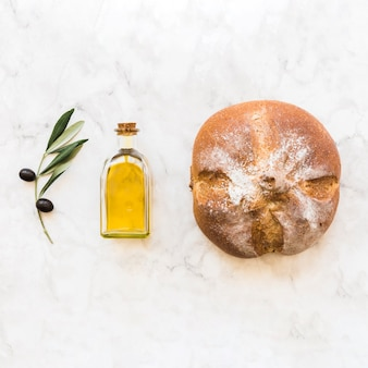 Black olive twig with oil bottle and round bun on white marble backdrop
