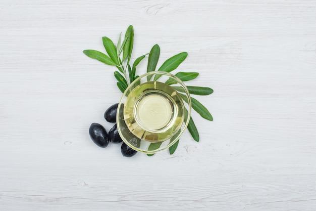 ブラックオリーブとガラスのオリーブオイルは、白い木の板にオリーブの葉の上から見ることができます。