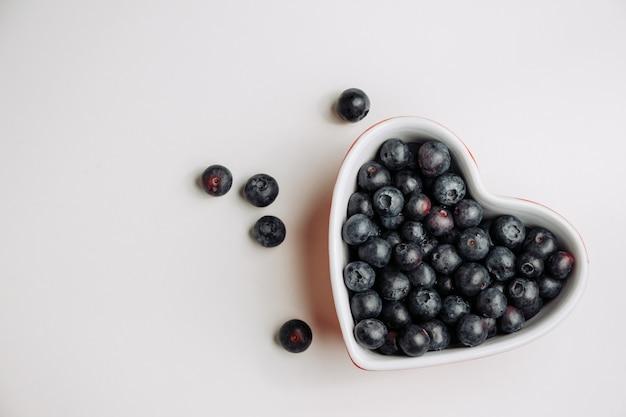 Le olive nere in un cuore hanno modellato la ciotola su una priorità bassa bianca. vista dall'alto.