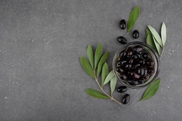 유리 그릇에 검은 올리브. 어두운 배경에 상위 뷰입니다.