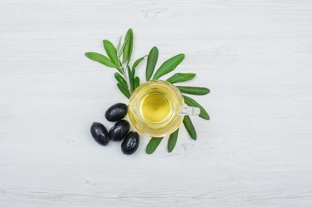 Black olives and olive oil in a glass jar with olive leaves top view on white wood plank