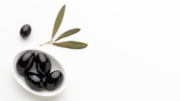 Black olives on plate with leaves with copy space