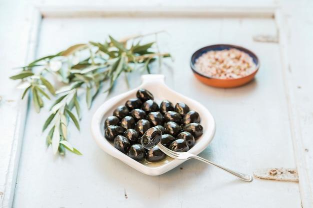 Black olives in white ceramic plate on board
