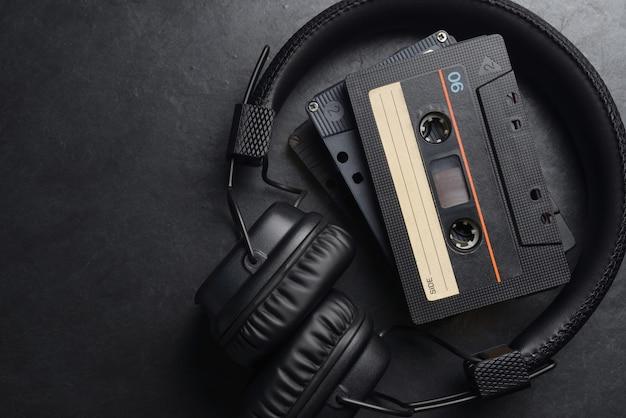 Черные накладные наушники и компакт-кассеты с аудиокассетами