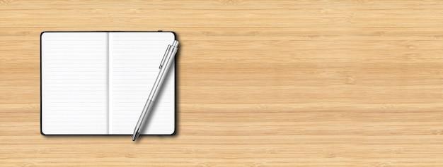 木製の背景に分離されたペンと黒のオープンラインのノートブックのモックアップ。横バナー