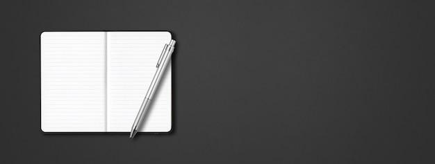 暗いテーブルで隔離されたペンと黒のオープンラインのノートブック