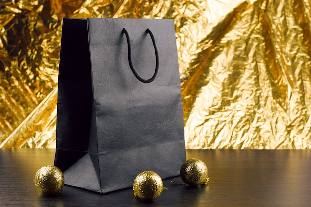 Black package and shiny golden christmas balls on a table on a goladen background