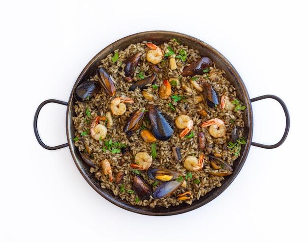 Черная паэлья с рисовыми креветками, мидиями и чернилами кальмара на белом фоне