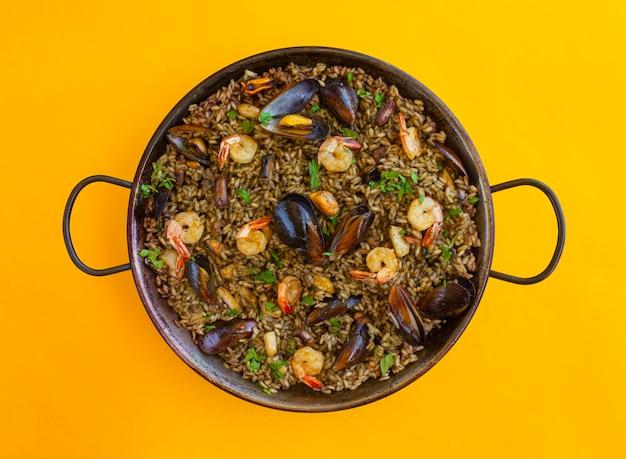 Черная паэлья с рисовыми креветками, мидиями и чернилами кальмаров на желтом фоне