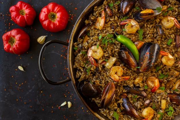 Черная паэлья с морепродуктами и чернилами кальмаров с помидорами на черном фоне