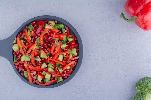 大理石の背景にピーマンとブロッコリーの横にある野菜サラダの黒い鍋。高品質の写真