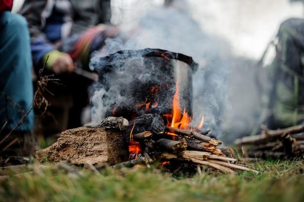 友達のグループの上にたき火の上に皿が立っている黒い鍋