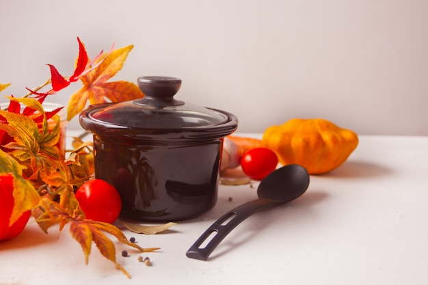 Black pan with autumn leaves and vegetables on white background
