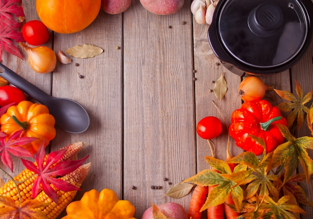 Black pan with autumn leaves and vegetables on the wooden background