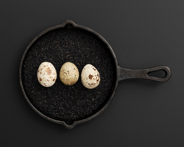 Black pan with poppy seeds and eggs