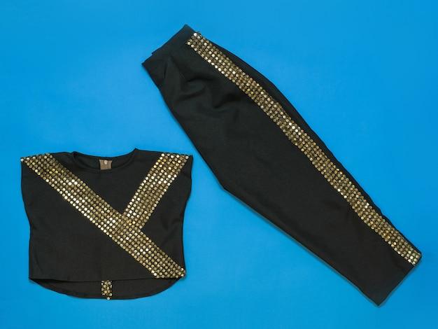 光沢のある仕上がりのブラックパンツとブラウス。婦人服とアクセサリーのトップビュー。フラットスタイル。