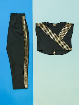 Black pants and blouse with a shiny finish. black with gold trim dance costume