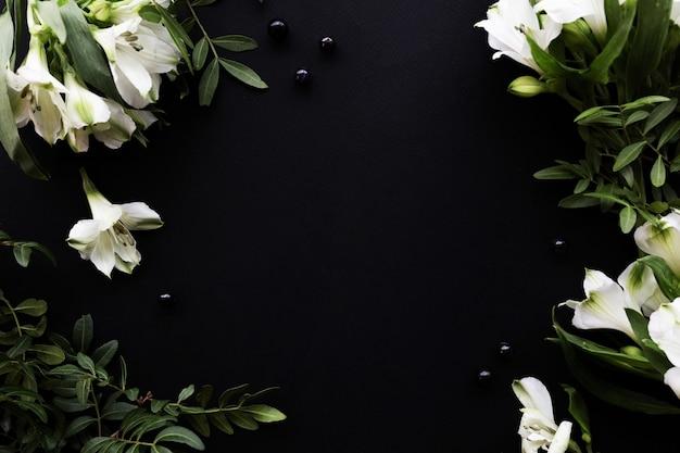 Черный бумажный фон с копией пространства вокруг - белый цветок альстромерии