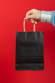 Black paper bag in hand on a red background.
