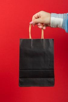 손에 빨간색 배경에 검은 종이 가방.