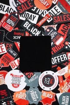 セールのオファーで多くのカラフルなラベルに横たわる黒の紙袋