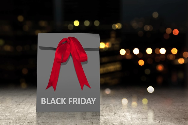 Black paper bag with a red ribbon with black friday text
