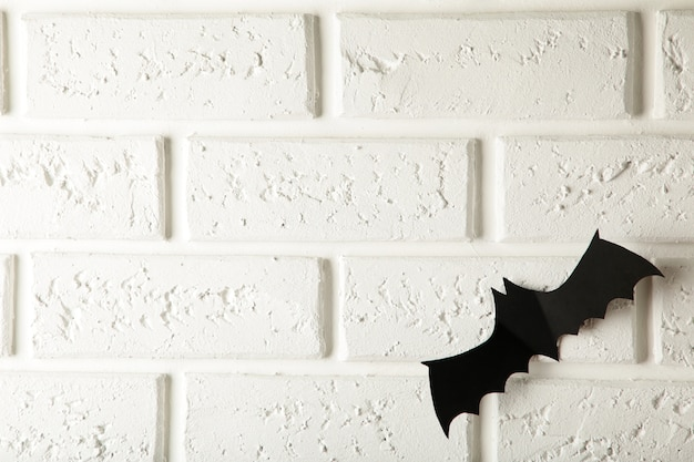 Черная бумажная летучая мышь пролетает над белой стеной