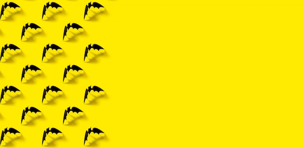 Black paper bat pattern with falling shadow on yellow.