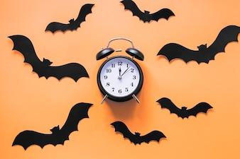 Black paper bats and alarm clock