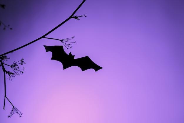 紫色のネオンの光の上を飛んでいる黒い紙コウモリ