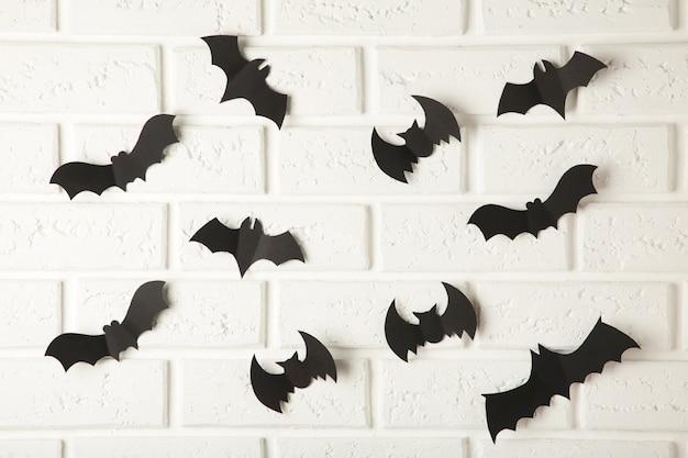 Черные бумажные летучие мыши летают над белой стеной