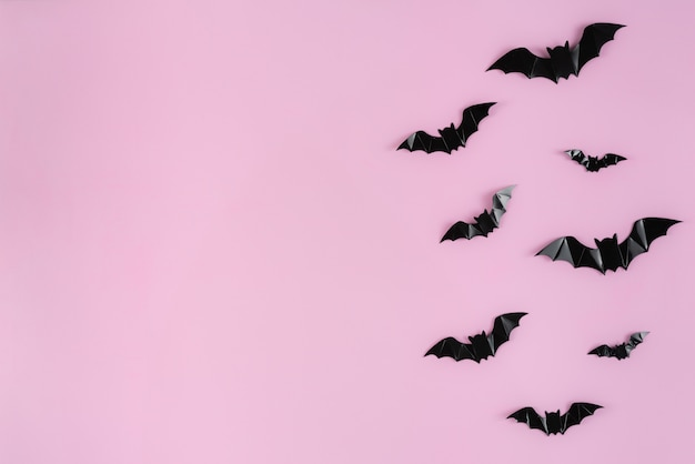 Black paper bats flying over pink