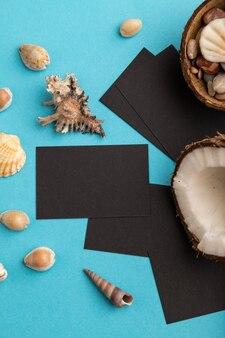 青いパステルカラーの背景にココナッツと貝殻の黒い紙の名刺。上面図、フラットレイ、