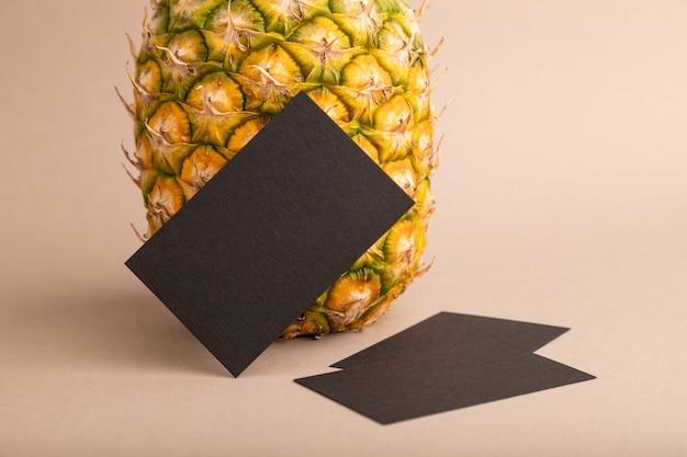 오렌지 파스텔 배경에 잘 익은 파인애플이 있는 검은색 종이 명함. 측면 보기, 복사 공간입니다.