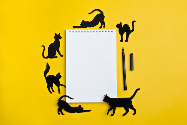 Black paper cats and a notebook